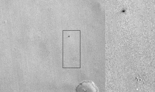 This image by NASA's Mars Reconnaissance Orbiter shows what appears to be the ExoMars lander's parachute (bright spot at bottom) and the impact site of the lander itself (dark patch at top).