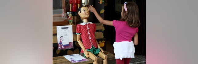 A child touches the nose of a Pinocchio puppet, a fictional character of a popular children's novel, at a woodwork souvenir shop in Vienna, Austria, August 21, 2015. REUTERS/Heinz-Peter Bader - RTX1P2LK