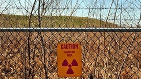 A radiation warning sign hangs on a fence at the West Lake landfill in Bridgeton, Mo.