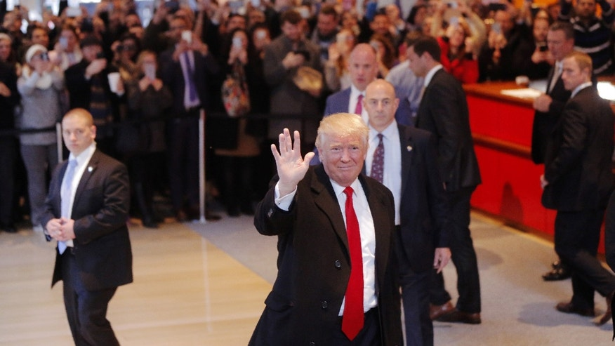 U.S. President elect Donald Trump reacts to a crowd gathered in the lobby of the New York Times building after a meeting in New York, U.S., Nov. 22, 2016. (REUTERS/Lucas Jackson)