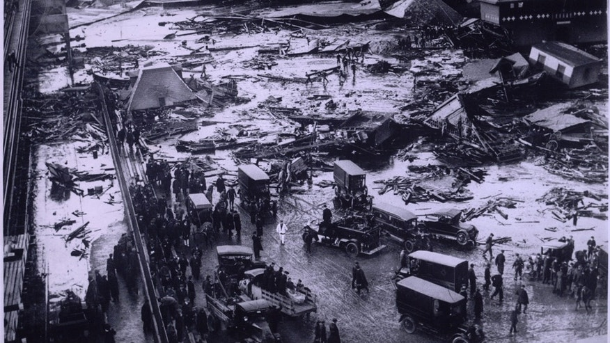 In 1919, a collapsed molasses tank sent a towering wave of the sticky mess through the streets, ensnaring everything from humans to horses to homes. The wreckage of the tank can be seen in the upper-right of the image.