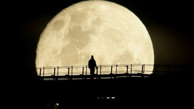 A man walks on the top span of the Sydney Harbour Bridge as the supermoon enters its final phase in Sydney, Australia, November 15, 2016.     REUTERS/Jason Reed     TPX IMAGES OF THE DAY      - RTX2TQHP