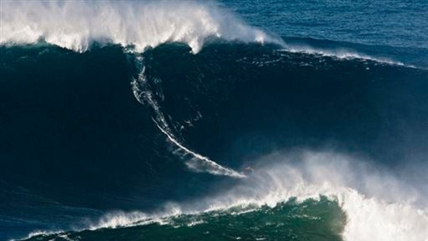 In this Nov. 1, 2011, file photo released by Nazare Qualifica/Polvo Concept, Garrett McNamara of Hawaii surfs what is being called the tallest wave ever ridden at Praia do Norte beach in Portugal. At 78 feet (24 meters), it's been certified by Guinness World Records.