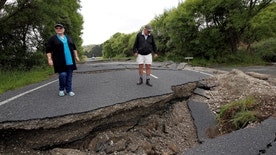 Local residents Chris and Viv Young look at damage caused by an earthquake along State Highway One, south of the township of Blenheim on New Zealand's South Island, November 14, 2016. REUTERS/Anthony Phelps   - RTX2THX3