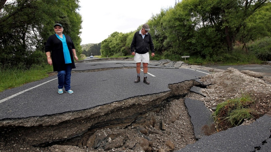 Local residents Chris and Viv Young look at damage caused by an earthquake along State Highway One, south of the township of Blenheim on New Zealand's South Island, November 14, 2016. (REUTERS/Anthony Phelps)