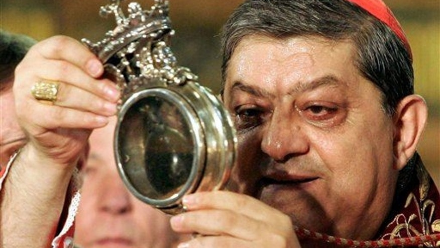 File photo - The archbishop of Naples holds a flask believed to contain drops of liquefied blood of San Gennaro in 2006.  (AP Photo/Salvatore Laporta, File)