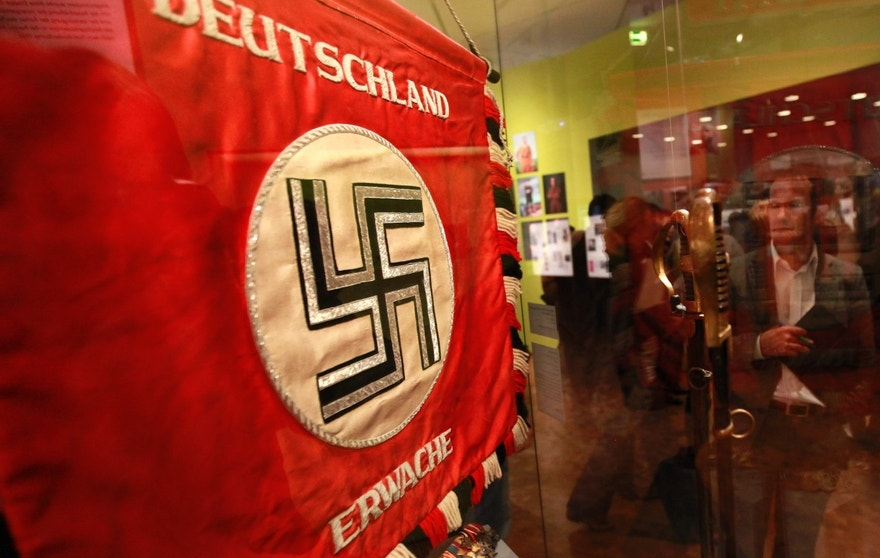 """A flag with the Nazi swastika is pictured at the media preview of """"Hilter und die Deutsche Volksgemeinschaft und Verbrechen"""" (Hitler and the German Nation and Crime) at the Deutsche Historisches Museum (German Historical Museum) in Berlin October 13, 2010. The exhibition will open to the public on October 15 and run till February 6, 2011. The words on the flag read """"Germany wake up"""".  REUTERS/Fabrizio Bensch (GERMANY - Tags: SOCIETY POLITICS) - RTXTEOV"""