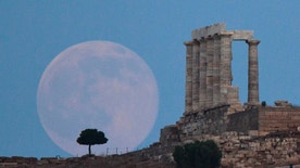 FILE - In this June 20, 2016 file photo, the full moon rises behind a tree next to the ruins of the ancient marble Temple of Poseidon, built in 444 BC, at Cape Sounion, southeast of Athens, on the eve of the summer solstice. On Wednesday, Jan. 11, 2017, a California-led research team reported that the moon formed within 60 million years of the birth of the solar system. Previous estimates ranged within 100 million years, all the way out to 200 million years of the solar system's creation. (AP Photo/Petros Giannakouris)