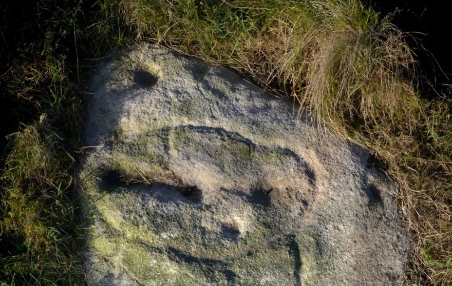 A stone Age carving on Baildon Moor which Gordon Holmes believes is a selfie of the artist under the symbol for Cassiopeia. See Ross Parry story RPYSELFIE; An amateur archaeologist has stumbled across Britain's first SELFIE - carved into a 4,000-year-old stone. Stunned Gordon Holmes, 64, discovered the ancient picture of a face etched into a rock on Baildon Moor in Yorkshire.He believes the carving was of the Stone Age artist himself.