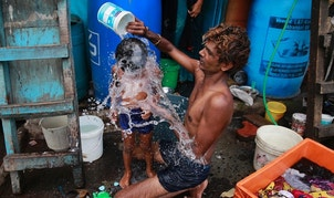 FILE - In this May 23, 2016, file photo, a man bath his son on a hot afternoon in a slum in Mumbai, India. For the third straight year, Earth set a record for the hottest year, NOAA and NASA announced. NASA says 2016 was warmer than 2015 - by a lot. It's mostly global warming with a little assist from the now-gone El Nino.(AP Photo/Rafiq Maqbool, File)