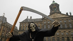 A street artist dressed as the grim reaper performs in front of the Dutch Royal Palace on Dam Square in Amsterdam March 19, 2013. REUTERS/Yves Herman (NETHERLANDS - Tags: SOCIETY TPX IMAGES OF THE DAY) - RTR3F7D3