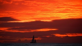 A sailboat passes in front of clouds lit up by the sunset sky off Waikiki in Hawaii, U.S., December 30, 2016. REUTERS/Kevin Lamarque - RTX2X0F4