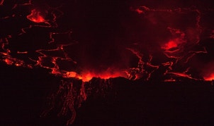 A lava lake with a diameter of 300 meters (500 feet) glows at night in the crater of Nyiragongo volcano near Goma in eastern Congo, August 30, 2010. The 3175m (10,400 ft) Nyiragongo erupted in 2002, killing nearly 50 people and forcing some 400,000 Goma residents to flee their homes as lava oozed through the city center, destroying about 15 per cent of the town. REUTERS/Finbarr O'Reilly (DEMOCRATIC REPUBLIC OF CONGO - Tags: ENVIRONMENT) - RTR2HPD5