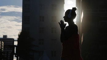 "A woman listens to music as the sun sets as seen between buildings on Boa Viagem beach in Recife June 30, 2014.  In a project called ""On the Sidelines"" Reuters photographers share pictures showing their own quirky and creative view of the 2014 World Cup in Brazil.  REUTERS/Brian Snyder    (BRAZIL - Tags: SPORT SOCCER WORLD CUP SOCIETY ENVIRONMENT) - RTR3WIPZ"