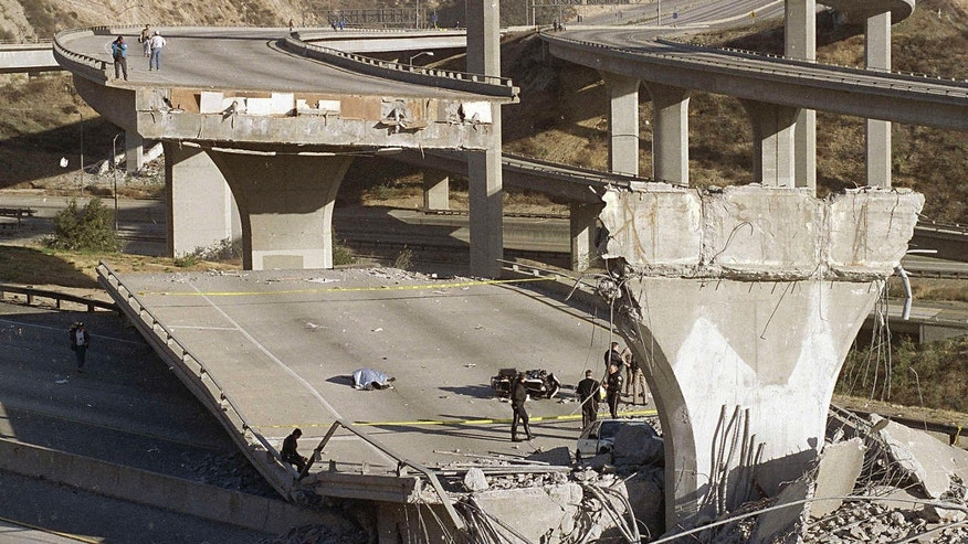 FILE - In this Jan. 17, 1994, file photo, the covered body of Los Angeles Police Officer Clarence Wayne Dean, 46, lies near his motorcycle which plunged off the State Highway 14 overpass that collapsed onto Interstate 5, after a magnitude-6.7 Northridge earthquake in Los Angeles.