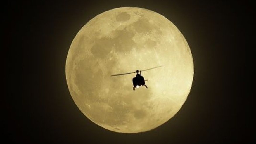 A helicopter flies in front of the Pink Moon on Monday in Las Vegas.
