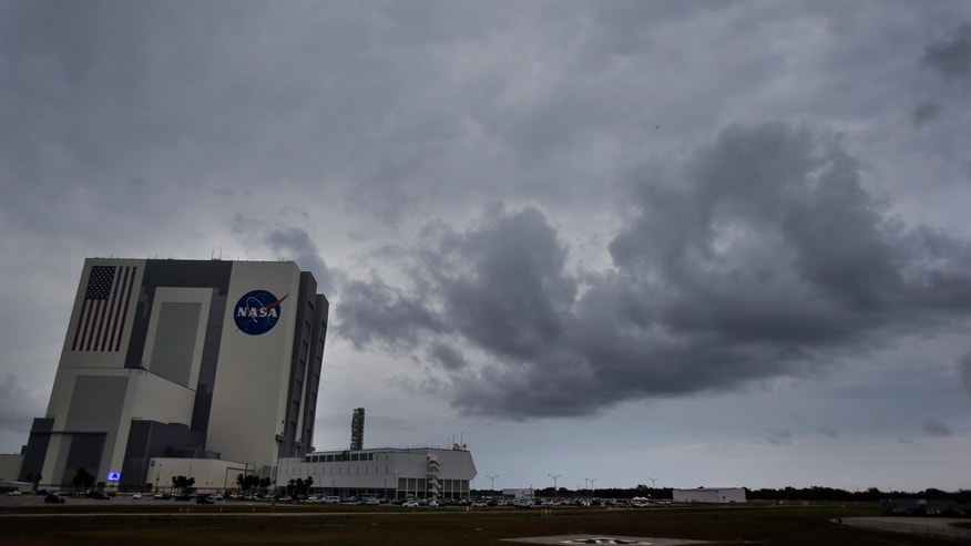 Storms clouds pass by the vehicle Assembly Building before a Falcon 9 SpaceX rocket launch was scrubbed because of bad weather at the Kennedy Space Center in Cape Canaveral, Fla., Thursday, June 1, 2017.