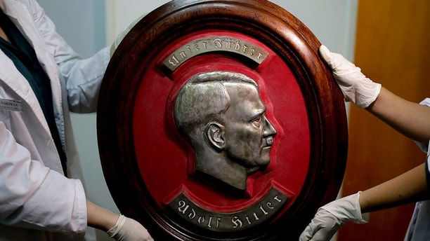 Members of the federal police show a bust relief portrait of Nazi leader Adolf Hitler at the Interpol headquarters in Buenos Aires, Argentina, Friday, June 16, 2017. In a hidden room in a house near Argentina's capital, police discovered on June 8th the biggest collection of Nazi artifacts in the country's history. Authorities say they suspect they are originals that belonged to high-ranking Nazis in Germany during World War II. (AP Photo/Natacha Pisarenko)