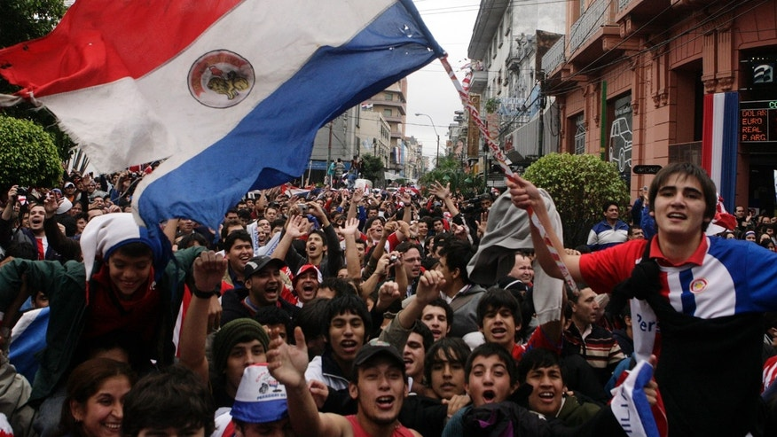 File photo - A Paraguayan soccer fan waves his national flag while celebrating Paraguay's victory over Japan to advance to the quarter-finals of the World Cup in Asuncion June 29, 2010. (REUTERS/Jorge Adorno)