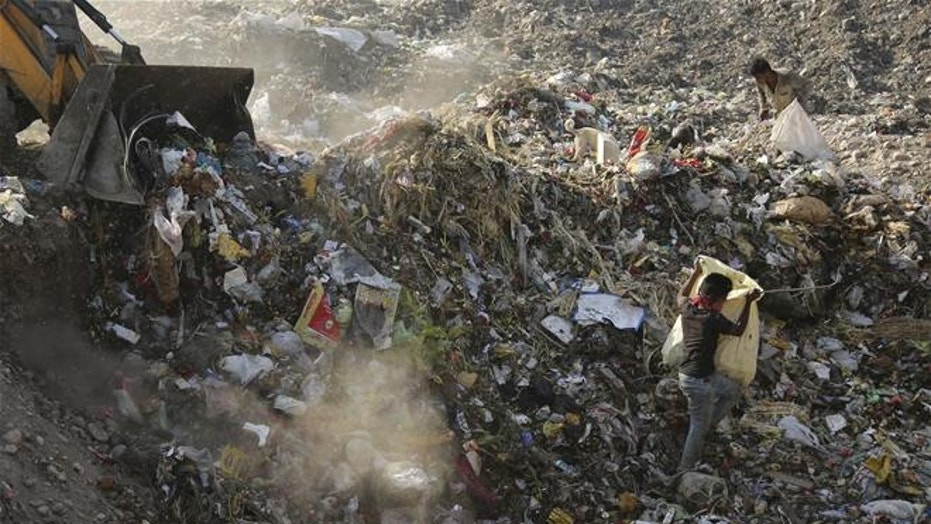 In this April 21, 2017, photo, an excavator dumps garbage at a landfill on the outskirts of Jammu, India. Much of the plastic we produce ends up in landfills.