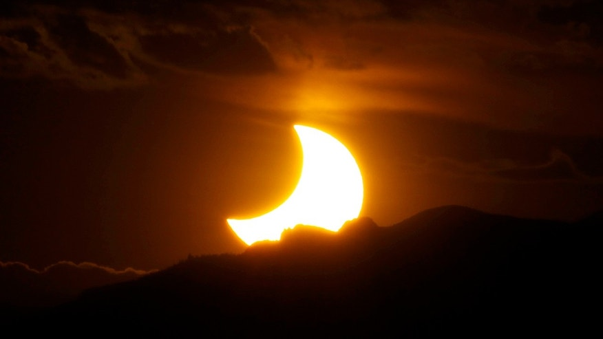 The annular solar eclipse is seen as the sun sets behind the Rocky Mountains from downtown Denver