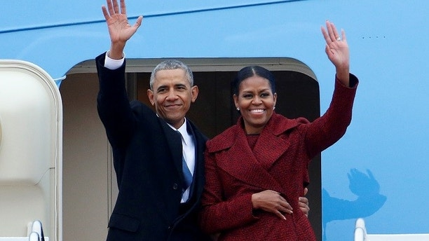 Former president Barack Obama waves with his wife Michelle as they board Special Air Mission 28000, a Boeing 747 which serves as Air Force One, at Joint Base Andrews, Maryland, U.S. January 20, 2017.   REUTERS/Brendan McDermid - RC14F2562160