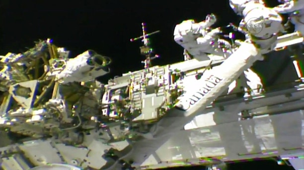 In this frame from NASA TV, Astronauts Mark Vande Hei, left, and Randy Bresnik work on the International Space Station on Thursday, Oct. 5, 2017. The astronauts went out on a spacewalk to give the International Space Station's big robot arm a new hand. (NASA TV via AP)