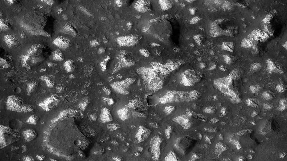 This view of a portion of the Eridania region of Mars shows blocks of deep-basin deposits that have been surrounded and partially buried by younger volcanic deposits. The image was taken by the Context Camera on NASA's Mars Reconnaissance Orbiter and covers an area about 12 miles wide. (Credits: NASA/JPL-Caltech/MSSS)