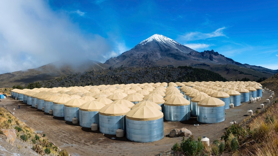 The HAWC gamma-ray observatory detects cosmic rays from its altitude of 13,500 feet in Mexico's Pico de Orizaba National Park. The Sierra Negro volcano looms large in the background.