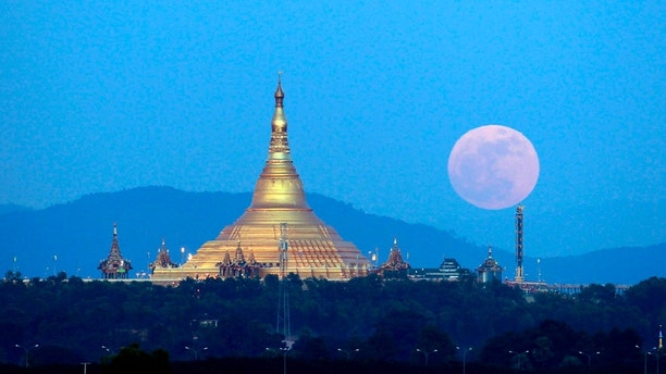 The moon rises behind the mountain range seen from Naypyitaw, Myanmar, Sunday, Dec. 3, 2017.  The Dec. 3 full moon is the first of three consecutive supermoons. The two will occur on Jan. 1 and Jan. 31, 2018.(AP Photo/Aung Shine Oo)