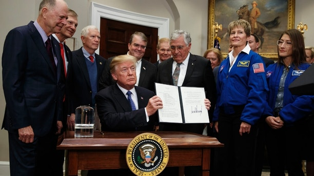 President Donald Trump holds up a policy directive to send American astronauts back to the moon, and eventually Mars, in the Roosevelt Room of the White House, Monday, Dec. 11, 2017, in Washington. (AP Photo/Evan Vucci)