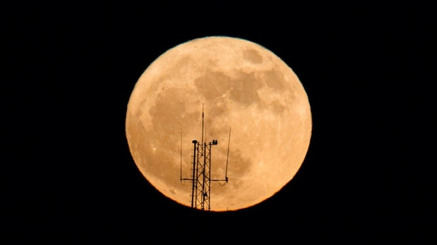 The moon rises over a building in Netanya, Israel, Sunday, Dec. 3, 2017. The Dec. 3 full moon is the first of three consecutive supermoons. The other two will occur on Jan. 1 and Jan. 31, 2018. (AP Photo/Ariel Schalit)