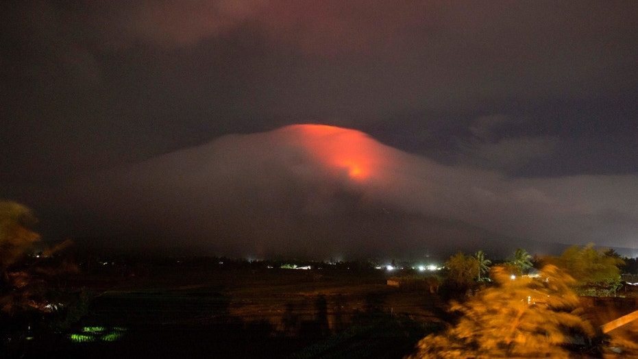 In this Sunday, Jan. 14, 2018, photo provided by Earl Recamunda, an orange glow is seen at the cloud-shrouded crater of Mayon volcano at Legazpi city, Albay province, about 340 kilometers (210 miles) southeast of Manila, Philippines. The Philippines' most active volcano rumbled back to life Sunday with lava rising to its crater in a gentle eruption that has prompted authorities to evacuate thousands of villagers. (Earl Recamunda via AP)