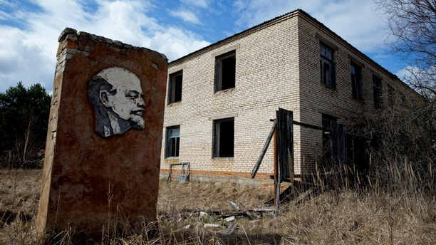 "A panel with a portrait of Soviet state founder Vladimir Lenin and an abandoned building are seen at the 30 km (19 miles) exclusion zone around the Chernobyl nuclear reactor in the abandoned village of Orevichi, Belarus, March 12, 2016. REUTERS/Vasily Fedosenko        SEARCH ""REVOLUTION RUSSIA"" FOR THIS STORY. SEARCH ""WIDER IMAGE"" FOR ALL STORIES. - RC13B4460000"