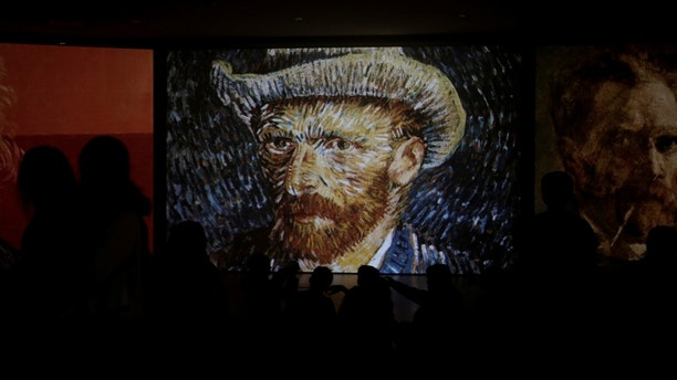 """Visitors look at a projection of Vincent Van Gogh's painting """"Self-Portrait with Grey Felt Hat"""" at the """"Van Gogh Alive"""" exhibition in Athens, Greece, November 10, 2017. Picture taken November 10, 2017. REUTERS/Alkis Konstantinidis - RC14DE1461B0"""