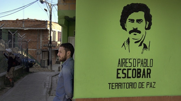 Doug Laux leans against a wall in the barrio with a stencil of Pablo Escobar?s face spray-painted on its surface.