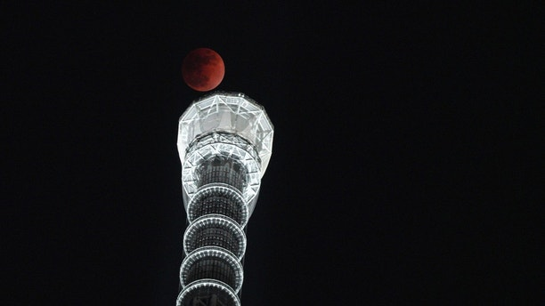 Lunar eclipse is seen over Tokyo Skytree in Tokyo Wednesday, Jan. 31, 2018.  On Wednesday, much of the world will get to see not only a blue moon which is a supermoon, but also a lunar eclipse, all rolled into one celestial phenomenon. (AP Photo/Eugene Hoshiko)