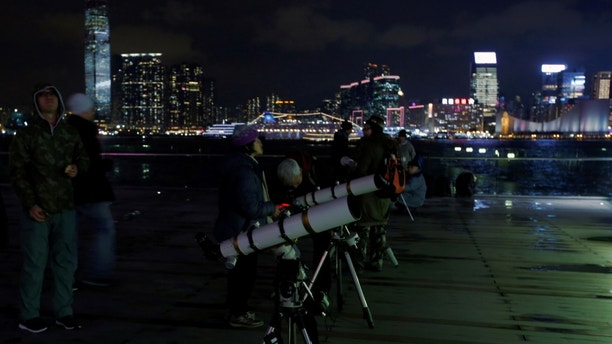 People set up telescopes on the waterfront for the super blue moon and eclipse in Hong Kong, China January 31, 2018. REUTERS/Bobby Yip - RC16F8115BB0