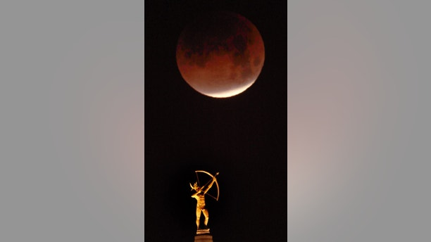 The eclipsing blood moon appears above the statue of Kansa Warrior Ad Astra atop the Kansas Statehouse in Topeka, Kan., Wednesday, Jan. 31, 2018. It's the first time in 35 years a blue moon has synced up with a supermoon and a total lunar eclipse.  Hawaii and Alaska have the best seats, along with the Canadian Yukon, Australia and Asia. The western U.S. should have good viewing, too, along with Russia. The U.S. East Coast, Europe and most of South America and Africa are out of luck for the eclipse. (AP Photo/Orlin Wagner)