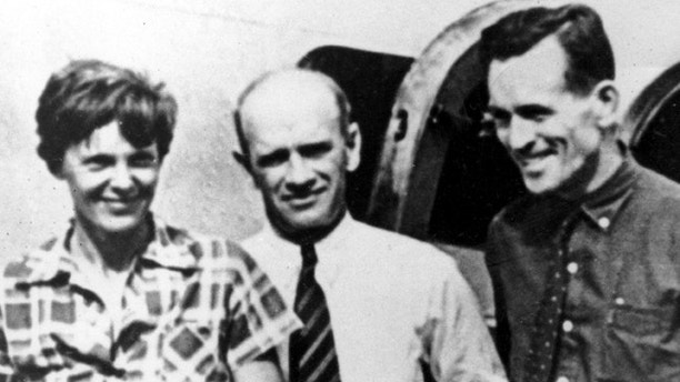 FILE - In this file photo taken on or about July 2, 1937, American aviator Amelia Earhart, left, and her navigator, Fred Noonan, right, pose beside their plane with gold miner F.C. Jacobs at Lae, New Guinea just before Earhart and Noonan took off in a flight to Howland Island on July 2, during which they disappeared somewhere in the Pacific. (AP Photo, File)