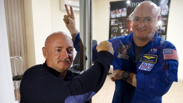 NASA astronaut Scott Kelly (R), and his twin brother Mark pose after a news conference at Baikonur cosmodrome March 26, 2015.