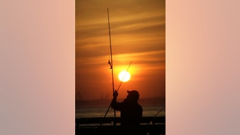 A man works with his fishing rod as the sun sets on the waterfront in the Red Hook section of the borough of Brooklyn  on Thursday, March 22, 2012 in New York. (AP Photo/Peter Morgan)