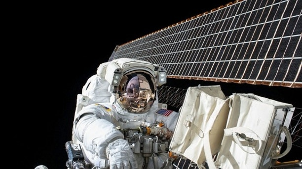 NASA astronaut Scott Kelly is seen during a spacewalk outside the International Space Station on Nov. 6, 2015. He and crewmate Tim Kopra will likely perform a surprise spacewalk on Monday, Dec. 21, to repair the station's stuck Mobile Transport