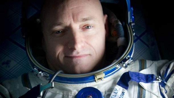 """Expedition 26 Commander Scott Kelly wears a blue wrist band that has a peace symbol, a heart and the word """"Gabby"""" to show his love of his sister-in-law U.S. Rep. Gabrielle Giffords as he rest onboard a Russian Search and Rescue helicopter shortly after he and fellow crew members Oleg Skripochka and Alexander Kaleri landed in their Soyuz TMA-01M capsule near the town of Arkalyk, Kazakhstan on Wednesday, March 16, 2011.  NASA Astronaut Kelly, Russian Cosmonauts Skripochka and Kaleri are returning from almost six months onboard the International Space Station where they served as members of the Expedition 25 and 26 crews. Photo Credit: (NASA/Bill Ingalls)"""