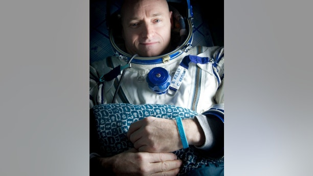"Expedition 26 Commander Scott Kelly wears a blue wrist band that has a peace symbol, a heart and the word ""Gabby"" to show his love of his sister-in-law U.S. Rep. Gabrielle Giffords as he rest onboard a Russian Search and Rescue helicopter shortly after he and fellow crew members Oleg Skripochka and Alexander Kaleri landed in their Soyuz TMA-01M capsule near the town of Arkalyk, Kazakhstan on Wednesday, March 16, 2011.  NASA Astronaut Kelly, Russian Cosmonauts Skripochka and Kaleri are returning from almost six months onboard the International Space Station where they served as members of the Expedition 25 and 26 crews. Photo Credit: (NASA/Bill Ingalls)"
