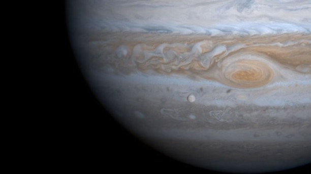 383787 03: The solar system's largest moon, Ganymede, is captured here alongside the planet Jupiter in this picture taken by NASA's Cassini spacecraft, December 3, 2000. Ganymede is larger than the planets Mercury and Pluto and Saturn's largest moon, Titan. Both Ganymede and Titan have greater surface area than the entire Eurasian continent on our planet. Cassini was 26.5 million kilometers (16.5 million miles) from Ganymede when this image was taken. The smallest visible features are about 160 kilometers (about 100 miles) across. (Photo courtesy of NASA/Newsmakers)