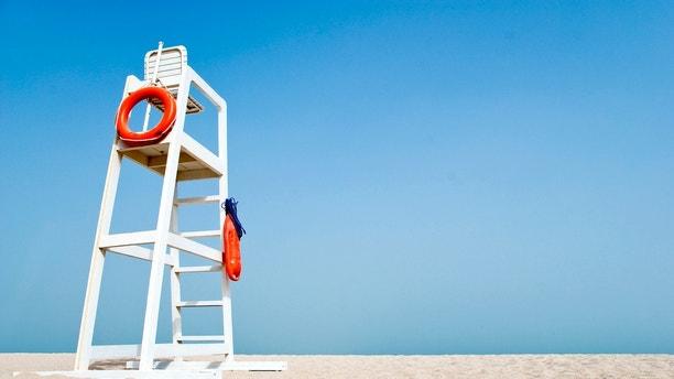 Empty white lifeguard chair on an empty beach with  orange life buoys hanging on the side.The chair stands against a clear blue sky in the sand.