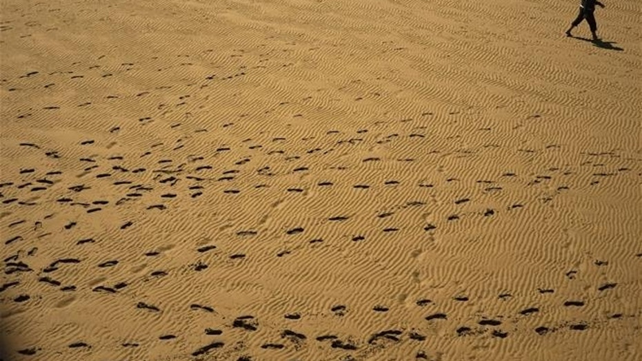 A person walks past beside footprints on the sand.