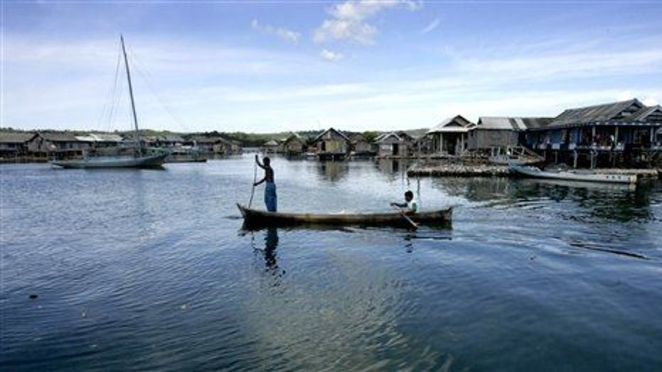 Men and women of the Bajau tribe row a boat at a fishing village on Kaledupa island, Southeast Sulawesi, Indonesia.
