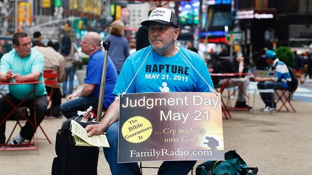A volunteer from the U.S. religious group Family Radio, a Christian radio network, hands out pamphlets with warnings of an impending Judgment Day at Times Square in New York May 13, 2011. The designation of May 21came from Family Radio president Harold Camping, who predicted that date through a series of mathematical calculations and the unraveling of codes behind the Bible story of the great flood. REUTERS/Shannon Stapleton (UNITED STATES - Tags: RELIGION SOCIETY) - GM1E75E08B501
